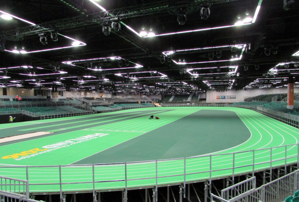 In this photo taken Monday, March 7, 2016, workers put the finishing touches on the track at the Oregon Convention Center in Portland, Ore. The track will host the U.S. indoor track and field championships starting Friday, March 11, and the IAAF World Indoor Championships the following week. (AP Photo/Anne M. Peterson)